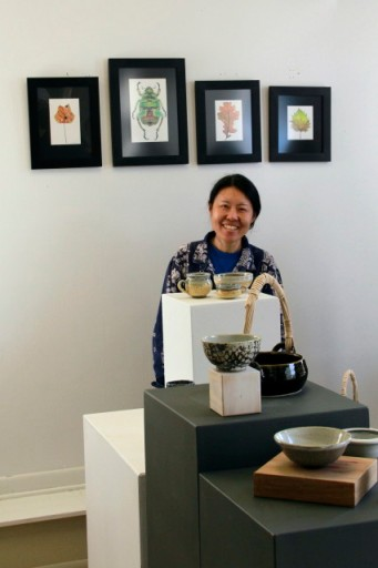 My pottery teacher, Miyako standing under my drawings and in front of my pottery pieces.